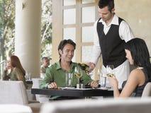 Coppie di Serving Wine To del cameriere Fotografia Stock Libera da Diritti