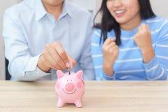 Coppie di sorriso che mettono una moneta in un porcellino salvadanaio rosa sul DES di legno immagini stock libere da diritti