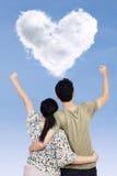 Coppie di successo con la nuvola di forma del cuore fotografie stock