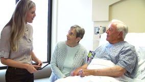 Coppie di Talking To Senior del consulente nella stanza di ospedale video d archivio