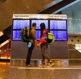 Coppie di viaggiatore con zaino e sacco a pelo all'aeroporto in Doha fotografie stock