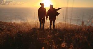 Coppie di viaggio che trascurano la vista sul mare durante il tramonto immagine stock