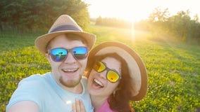 Coppie di viaggio felici che rendono a selfie i colori soleggiati di estate al tramonto stock footage