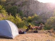 Coppie di viaggio su uno sfondo naturale Turisti che si siedono sulle sedie in un parco nazionale Concetto di distensione Copi lo Fotografia Stock