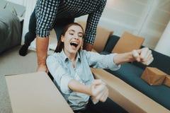 Coppie divertendosi durante muoversi in nuovo appartamento immagine stock