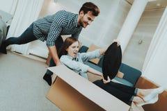 Coppie divertendosi durante muoversi in nuovo appartamento fotografia stock libera da diritti