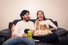 Coppie divertendosi televisione di sorveglianza, scorrente Film e serie Fotografia Stock