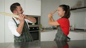 Coppie divertenti che fingono lotta con gli strumenti degli utensili mentre cucinando a casa insieme Marito e moglie divertendosi video d archivio