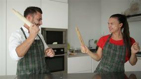 Coppie divertenti che fingono lotta con gli strumenti degli utensili mentre cucinando a casa insieme Marito e moglie divertendosi archivi video