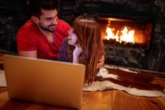 Coppie divertenti che mettono su pavimento e che guardano film sul computer portatile fotografie stock