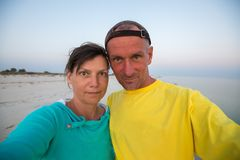 Coppie divertenti dei viaggiatori che prendono selfie sulla spiaggia abbandonata Fotografia Stock
