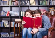 Coppie dolci alla biblioteca che si nasconde dietro un libro Immagine Stock