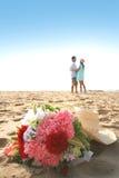 Coppie dolci sulla spiaggia con il mazzo Fotografia Stock