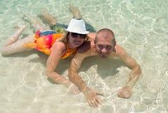 Coppie durante le vacanze estive sulla spiaggia che bagna nell'acqua Immagine Stock Libera da Diritti