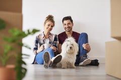 Coppie e cane sorridenti nella loro nuova casa immagini stock libere da diritti