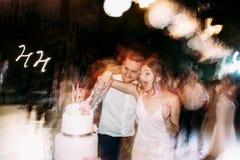 Coppie e torta nunziale nella sera Fotografia Stock Libera da Diritti