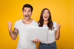 Coppie emozionanti che gridano e che tengono computer portatile su fondo immagini stock