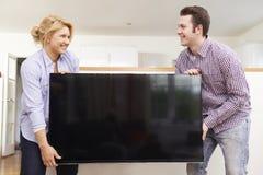 Coppie emozionanti che installano nuova televisione a casa Immagini Stock