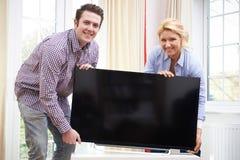Coppie emozionanti che installano nuova televisione a casa immagine stock libera da diritti