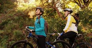 Coppie esaurite di ciclismo di montagna che prendono una rottura video d archivio