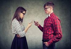 Coppie facendo uso degli smartphones completamente assorbiti nella vita online, non parlando l'un l'altro, affrontante uno un alt fotografia stock