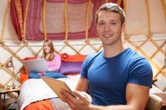Coppie facendo uso dei dispositivi di Digital su vacanza in campeggio di Yurt Fotografie Stock