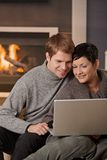 Coppie facendo uso del computer portatile all'inverno Fotografia Stock