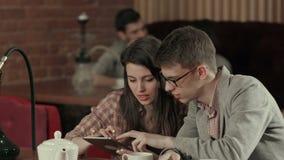 Coppie facendo uso della compressa digitale e narghil? di fumo in caff? di Shisha archivi video