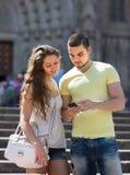 Coppie facendo uso della mappa allo smartphone Fotografia Stock Libera da Diritti