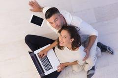 Coppie facendo uso della visualizzazione superiore dei computer portatili e della compressa Fotografia Stock Libera da Diritti