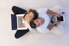 Coppie facendo uso della visualizzazione superiore dei computer portatili e della compressa Fotografia Stock