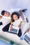 Coppie facendo uso della visualizzazione superiore dei computer portatili e della compressa immagine stock libera da diritti