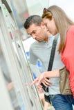 Coppie facendo uso dello sguardo a macchina del biglietto sconcertante fotografie stock