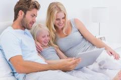 Coppie facendo uso di un computer portatile con la loro figlia Immagini Stock Libere da Diritti