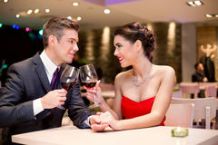 Coppie felici alla tostatura della tavola del ristorante fotografia stock libera da diritti