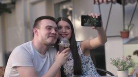 Coppie felici alle feste che prendono selfie mentre sedendosi alla tavola fuori del caffè video d archivio
