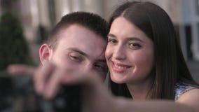 Coppie felici alle feste che prendono selfie mentre sedendosi alla tavola fuori del caffè archivi video
