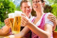 Coppie felici in birra bevente del giardino della birra immagini stock
