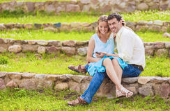 Coppie felici caucasiche che hanno buon tempo insieme all'aperto usando Fotografia Stock