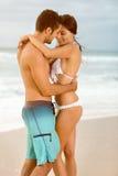 Coppie felici che abbracciano sopra la spiaggia di tramonto immagine stock