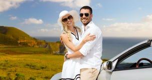 Coppie felici che abbracciano vicino all'automobile convertibile immagini stock