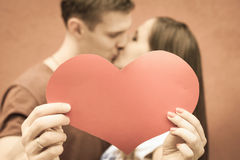Coppie felici che baciano e che tengono cuore al fondo rosso della parete Fotografia Stock