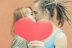 Coppie felici che baciano e che tengono cuore al fondo rosso della parete Immagini Stock Libere da Diritti