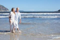 Coppie felici che camminano a piedi nudi sulla spiaggia Immagini Stock Libere da Diritti
