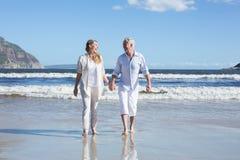 Coppie felici che camminano a piedi nudi sulla spiaggia Fotografia Stock