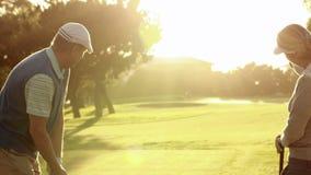 Coppie felici che collocano sul tee fuori al campo da golf video d archivio