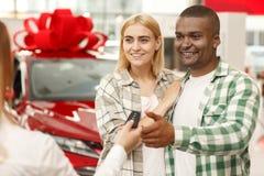 Coppie felici che comprano insieme nuova automobile alla gestione commerciale fotografie stock