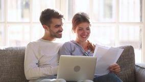 Coppie felici che controllano servizio facile per pagare le fatture domestiche online stock footage