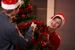 Coppie felici che decorano l'albero di Natale Fotografie Stock