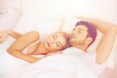 Coppie felici che dormono a letto a casa fotografie stock